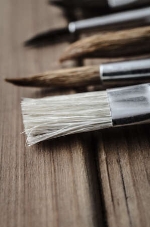 lain: Close up of a variety of artists paintbrushes, lying on a wood plank table. Stock Photo