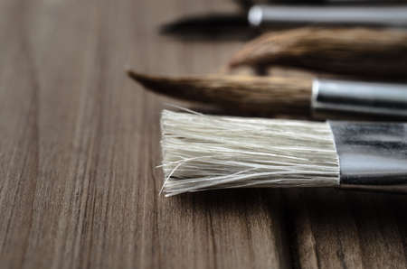 Side view close up of a variety of artists paintbrushes, laid out in a row on a wood plank table. Stock Photo