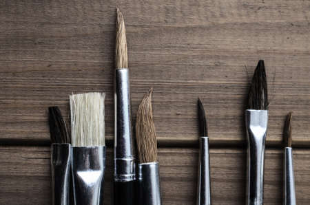 Overhead photograph of a variety of artists paintbrushes arranged on old, faded wood.