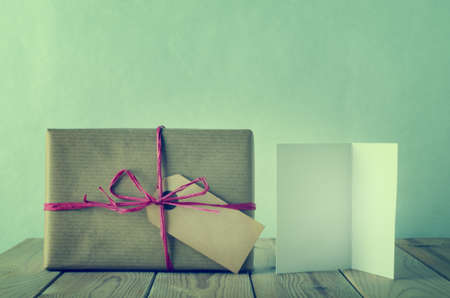 cross processed: A gift box with blank label, wrapped in simple brown paper and tied with pink raffia bow on a wooden table.  An opened, blank  greeting card faces front.  Cross processed to give a retro or vintage style. Stock Photo
