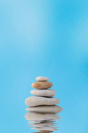watery: A pile of five stacked stones with a watery rippled reflection below and blue sky with light white cloud haze in the background.