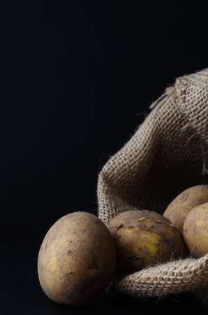 unwashed: Raw, non lavate, patate con la buccia, fuoriuscita di sacco di iuta. Illuminazione Moody, superficie nera e lo sfondo.