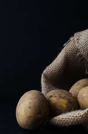 unwashed: Raw, unwashed, unpeeled potatoes, spilling out of hessian sack.  Moody lighting, black surface and background. Stock Photo