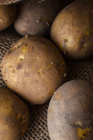 portrait orientation: Raw, unwashed, unpeeled potatoes with flaking peel, shot from above in hessian sack.  Dark lighting. Stock Photo