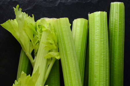 upright row: Overhead shot of leafy and leafless green celery sticks, loosely lined up and stacked on black slate.