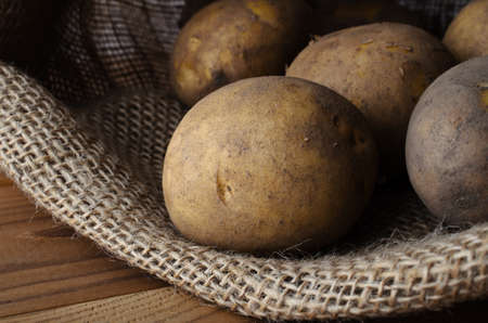 Raw, unwashed, unpeeled potatoes in opened hessian sack, lain on wood planked table. Stock Photo