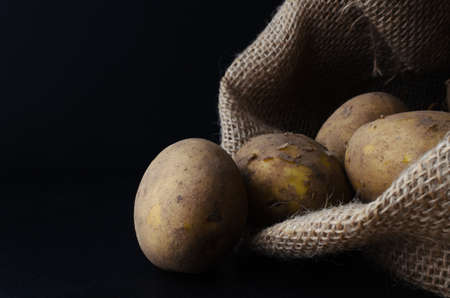 unwashed: Raw, unwashed, unpeeled potatoes, spilling out of hessian sack on to black slate surface.  Moody lighting, black background. Stock Photo