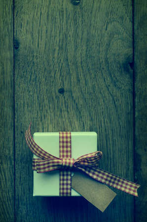 cross processed: Overhead shot of a white box on old wood plank table, tied to a bow in red and cream gingham (checked) ribbon, with vintage effect parchment style label left blank for copy space.  Cross processed for retro appearance.