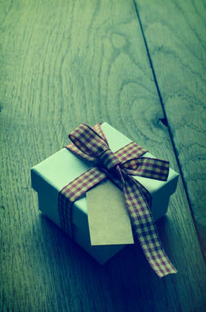 cross processed: A white gift box with closed lid, tied to a bow with red and cream gingham ribbon.  Blank vintage label facing upwards. Cross processed for retro appearance.