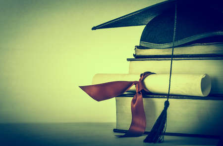 A mortarboard and graduation scroll, tied with red ribbon, on a stack of old battered books with empty space to the left for copy.  Cross processed with vignette for retro or vintage effect.