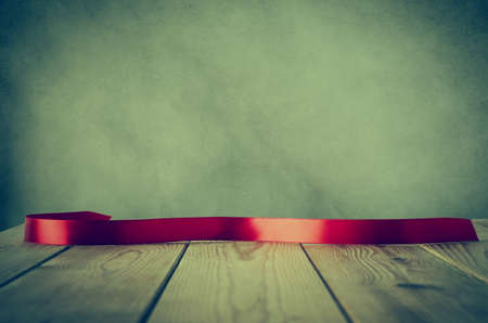 cross processed: A red satin ribbon, curved and facing front to provide copy space for message, placed on a wood plank table against parchment background.  Cross processed with vignette for retro or vintage style.