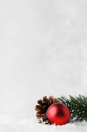 A Christmas border and background with red bauble, fir cone and green branch, nestling in white fake snow in lower right corner.  Twinkling stars in background. Stock Photo