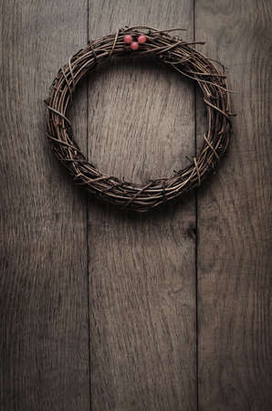 uncluttered: Christmas concept. A simple, natural Christmas wreath woven from soft twigs with artificial red berries, hanging on an old, weathered oak wood plank door.  Processed with low saturation and vignette to give vintage or retro effect.