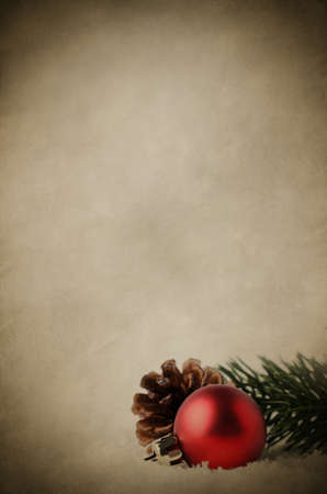lain: Christmas border and background with red bauble, fir cone and green branch, nestling in white fake snow.  Parchnmet texture gives vintage effect with subtle twinkling stars in background. Stock Photo
