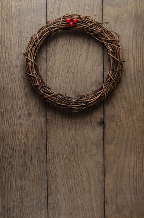 uncluttered: Christmas concept. A simple, natural Christmas wreath woven from soft twigs with artificial red berries, hanging on an old, weathered oak wood plank door.