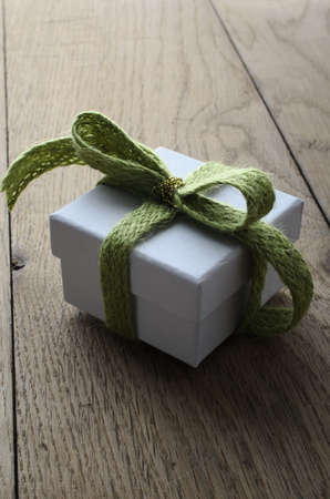 wooly: Slightly elevated view of a white, lidded square gift box on an old oak planked table, tied to a bow with a soft green wooly fabric ribbon, and wrapped with a shiny gold thread.