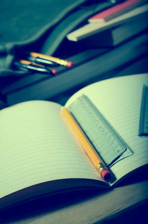 deberes: Escuela de escritorio o una escena tarea. Un cuaderno abierto en la mesa con lápiz y regla. maletín abierto en el fondo. Cruz procesado para el efecto retro.