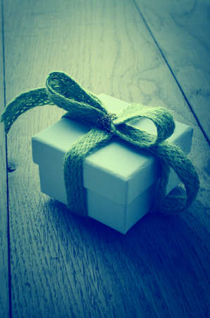 cross processed: Slightly elevated view of a white, lidded square gift box on an old oak planked table, tied to a bow with a soft green wooly fabric ribbon, and wrapped with a shiny gold thread.  Cross processed for retro or vintage effect.