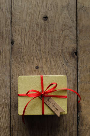 centred: Overhead shot of a simple yellow gift box on an old oak wood planked table, tied to a bow with red satin ribbon, with a vintage style merry christmas tag facing upwards.