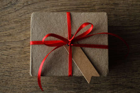 centred: A plain brown cardboard gift box with blank vintage style notched gift tag, tied to a bow with thin red satin ribbon.  Overhead shot on oak wood table. Stock Photo