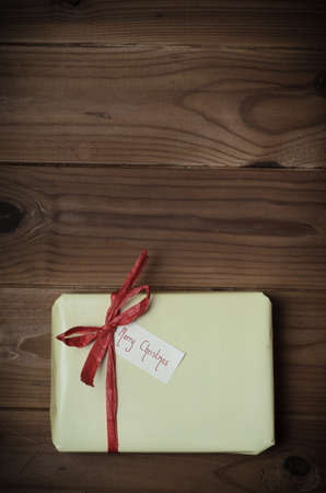 adjusted: Overhead of a gift package wrapped in pale yellow and tied to bow with red raffia ribbon on wood planked surface.  Gift label facing upwards reads Merry Christmas.  Hues adjusted and vignette added for retro or vintage style effect.