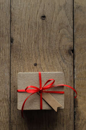 centred: Overhead shot of a simple brown gift box on an old oak wood planked table, tied to a bow with red satin ribbon, with a blank vintage style parcel tag facing upwards.
