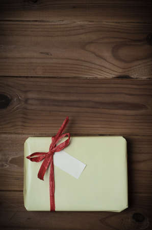adjusted: Overhead of a gift package wrapped in pale yellow and tied to bow with red raffia ribbon on wood planked surface.  Hues adjusted and vignette added for retro or vintage style effect.