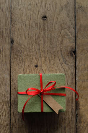 centred: Overhead shot of a simple green gift box on an old oak wood planked table, tied to a bow with red satin ribbon, with a blank vintage style parcel tag facing upwards. Stock Photo