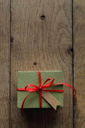 generosity: Tiro de arriba de una caja de regalo verde simple en una vieja mesa de tablones de madera de roble, atado a un lazo con la cinta de satén rojo, con una etiqueta en blanco parcela estilo vintage mirando hacia arriba.