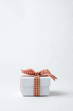 closed ribbon: A simple, small white lidded gift box, closed and tied to a bow with a red gingham checked ribbon on plain blackground.