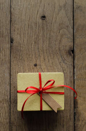 centred: Overhead shot of a simple yellow gift box on an old oak wood planked table, tied to a bow with red satin ribbon, with a blank vintage style parcel tag facing upwards.