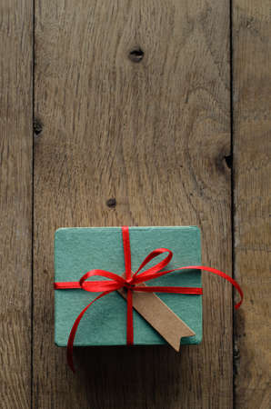 centred: Overhead shot of a turquoise gift box on an old oak wood planked table, tied to a bow with red satin ribbon, with a blank vintage style message tag facing upwards.