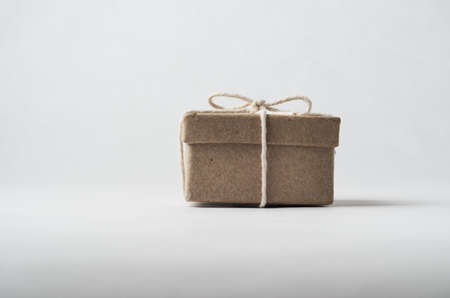 despatch: Eye level shot of a simply packaged brown cardboard box with lid, tied to a bow with string.  Off white background.