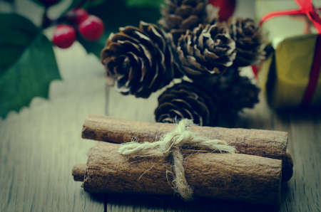 cross processed: Cinnamon sticks, tied in a bundle with string on an oak table with Christmas holly, fir cones and a gold wrapped gift box in the background.  Cross processed for retro or vintage effect.