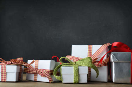 lazo regalo: Una variedad de regalos de Navidad en una fila desordenada que se extiende más allá de cada lado del marco. Colocado en un escritorio con fondo de la pizarra.