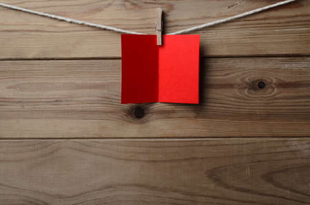 A blank, red greetings or Christmas card, pegged to string against old wood planked background.  Copy space on card and below. Stock Photo