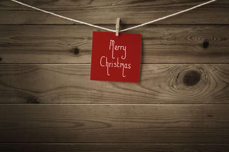vignetted: Merry Christmas message handwritten on a square of festive red note paper and pegged to a string washing line.  Wood plank background with low saturation and vignette for retro or vintage feel.