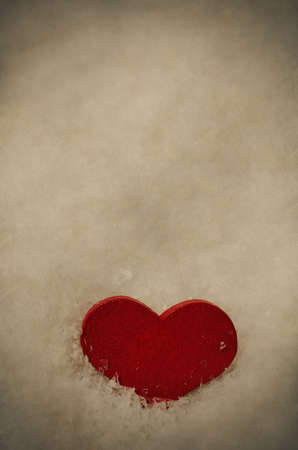 kind hearted: A red wooden heart, nestling upright in white artificial snow with sprinkled snowflakes on its surface.  Aged and weathered vintage effect with vignette.