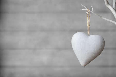 중립 나무 판자 소프트 포커스 배경 가진 흰색 인공 나무의 지점에서 걸려 흰색 페인트 심장. 스톡 콘텐츠
