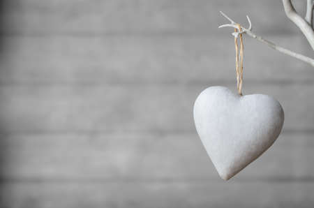 A white painted heart, hanging from branch of white artificial tree, with neutral  wood plank soft focus background. Фото со стока