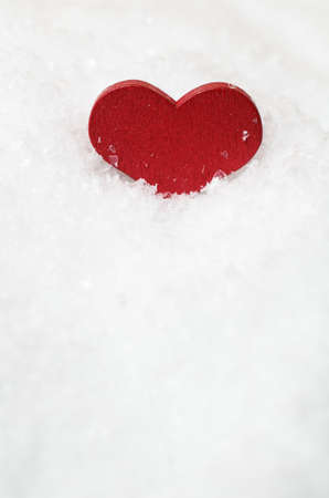 nestled: A red wooden heart, upright and nestled in artificial white snow in top section of frame with copy space below.