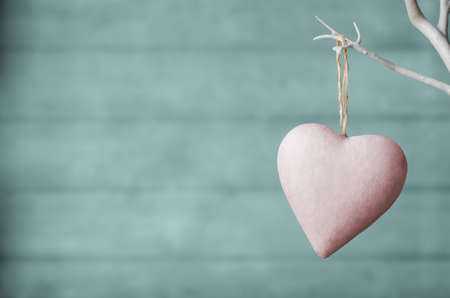 A pink painted heart, hanging from branch of white artificial tree, with faded turquoise wood plank soft focus background. Pastel hues.