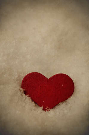 kind hearted: A red, wooden heart, settled upright in fallen snow (artificial) and facing forwards just below eye level.  Copy space above. Aged, weathered and vignetted for vintage effect. Stock Photo