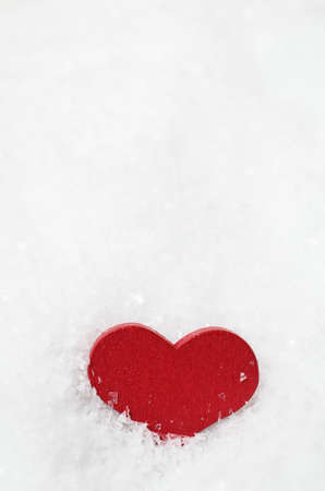 A red wooden heart, nestling upright in white artificial snow with sprinkled snowflakes on its surface. Stock Photo - 49140412