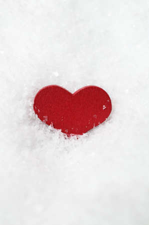 centred: A red wooden heart, partly submerged in white artificial snow, vertically centred with copy space above and below. Stock Photo