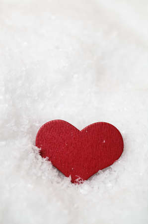 settled: A red, wooden heart, settled upright in fallen snow (artificial) and facing forwards just below eye level.  Copy space above.