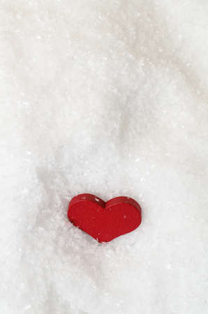 kind hearted: Red heart in white artificial snow, viewed from above as though looking down.  Copy space above and below.
