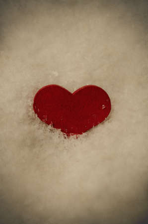 centred: A red wooden heart, partly submerged in white artificial snow, vertically centred with copy space above and below.  Aged and weathered for vintage effect. Stock Photo