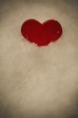 kind hearted: A red wooden heart, upright and nestled in artificial white snow in top section of frame with copy space below. Aged and weathered vintage effect with vignette. Stock Photo