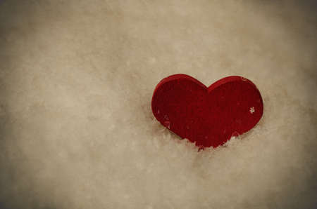 nestled: A red wooden heart, nestled in white artificial snow. Aged and weathered vintage effect with vignette.